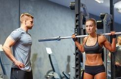 Man and woman with barbell flexing muscles in gym. Sport, fitness, bodybuilding, lifestyle and people concept - men and women with barbell flexing muscles in gym Royalty Free Stock Photography