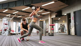 Man and woman with barbell flexing muscles in gym. Sport, fitness, lifestyle, weightlifting and people concept - woman and personal trainer doing lunge with stock footage