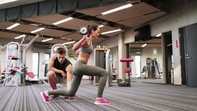 Man and woman with barbell flexing muscles in gym. Sport, fitness, lifestyle, weightlifting and people concept - woman and personal trainer doing lunge with stock video