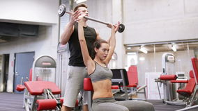 Man and woman with barbell flexing muscles in gym. Sport, fitness, lifestyle, weightlifting and people concept - young woman and personal trainer with barbell stock footage