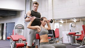 Man and woman with barbell flexing muscles in gym. Sport, fitness, lifestyle, weightlifting and people concept - young woman and personal trainer with barbell stock video