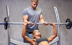 Man and woman with barbell flexing muscles in gym Stock Photography
