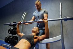 Man and woman with barbell flexing muscles in gym Stock Images