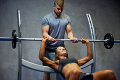 Man and woman with barbell flexing muscles in gym Stock Photos