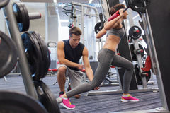 Man and woman with barbell flexing muscles in gym Stock Image
