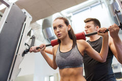 Man and woman with barbell flexing muscles in gym Stock Photo