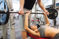 Man and woman with barbell flexing muscles in gym Royalty Free Stock Image