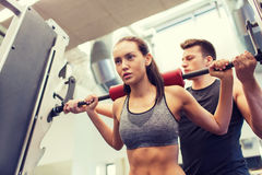 Man and woman with barbell flexing muscles in gym. Sport, fitness, teamwork, weightlifting and people concept - young women and personal trainer with barbell Stock Photo