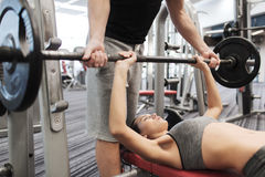 Man and woman with barbell flexing muscles in gym. Sport, fitness, teamwork, weightlifting and people concept - young women and personal trainer with barbell Royalty Free Stock Image