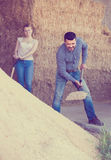 Man and woman in the barn. Joyful smiling  men and women with shovel working in farm housing . Focus on man Royalty Free Stock Images