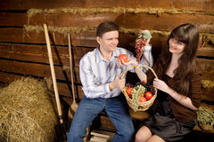 Man and woman with basket of fruit on bench. Smiling man and young woman with basket of fruit sitting on bench in wooden log hut stock images
