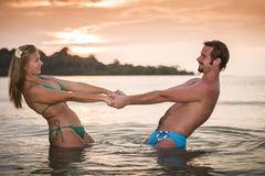Man and woman on the beach having fun at sunset Stock Photo