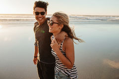 Man and woman on beach holiday. Portrait of romantic young couple walking on sea shore. Man and women on beach holiday during summertime Royalty Free Stock Images