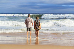 Man and woman on beach looking at sea Stock Photography