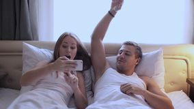 Man and woman in bed doing selfie. Girl with a guy taking pictures of yourself on the front camera. Smartphone stock video footage