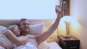 Man and woman in bed doing selfie. Girl with a guy taking pictures of yourself on the front camera. Smartphone stock footage
