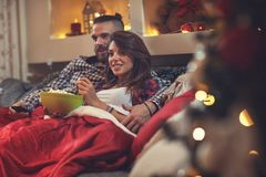 Man and woman in bed watching tv and eating pop corn. Young men and women in bed watching tv and eating pop corn Stock Photography