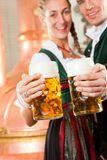 Man and woman with beer glass in brewery. Man and women with beer glasses in Bavarian tracht in brewery in front of a brew kettle Stock Photo