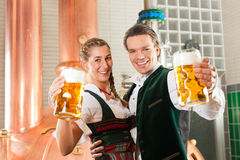 Man and woman with beer glass in brewery. Man and women with beer glasses in Bavarian tracht in brewery in front of a brew kettle Royalty Free Stock Photography