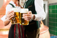 Man and woman with beer glass in brewery. Man and women with beer glasses in Bavarian tracht in brewery in front of a brew kettle Stock Images