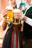 Man and woman with beer glass in brewery. Man and women with beer glasses in Bavarian tracht in brewery in front of a brew kettle Stock Image