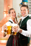 Man and woman with beer glass in brewery. Man and women with beer glasses in Bavarian tracht in brewery in front of a brew kettle Royalty Free Stock Images
