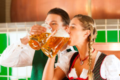 Man and woman with beer glass in brewery. Young men and women in traditonal Tracht with beer glass in brewery, in front of brewing kettle Royalty Free Stock Images