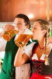 Man and woman with beer glass in brewery. Young men and women in traditonal Tracht with beer glass in brewery, in front of brewing kettle Royalty Free Stock Photo