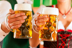 Man and woman with beer glass in brewery. Young men and women in traditonal Tracht with beer glass in brewery, in front of brewing kettle Stock Images