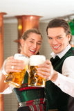 Man and woman with beer glass in brewery. Man and woman with beer glasses in Bavarian tracht in brewery in front of a brew kettle Royalty Free Stock Images