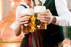 Man and woman with beer glass in brewery. Man and woman with beer glasses in Bavarian tracht in brewery in front of a brew kettle Royalty Free Stock Photos