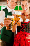 Man and woman with beer glass in brewery. Young men and women in traditonal Tracht with beer glass in brewery, in front of brewing kettle Royalty Free Stock Photography