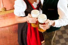 Man and woman with beer glass. Man and women with beer glass in brewery Royalty Free Stock Photos