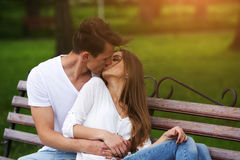 Man and woman on a bench in the park. Beautiful young couple sitting on a bench in the park Royalty Free Stock Photography