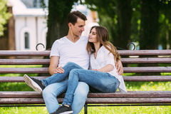 Man and woman on a bench in the park Stock Images