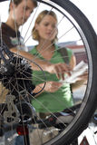 Man and woman in bicycle shop, view through wheel Stock Images