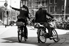 Man and woman on the bikes,  Amsterdam. Man and woman on the bikes on the street. Black and white. Netherlands, Amsterdam Royalty Free Stock Photo