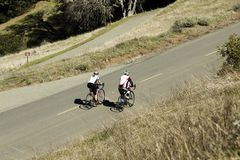 Man And Woman Biking On Mountain Road Royalty Free Stock Images