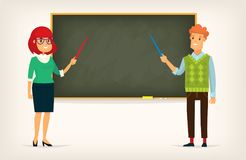 Man and woman at blackboard. A man and a woman standing near a blackboard at school or university are pointing at blackboard teaching a lesson Stock Image
