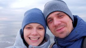 Man and woman bloggers on selfie video smiling and talking at sea in winter. stock footage