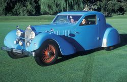 A man and woman in a blue Bugatti automobile at a vintage car show in Pebble Beach, California, ca. 1985. Royalty Free Stock Photos