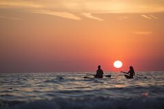 Man and Woman Boat Rowing in Sea during Golden Hour Royalty Free Stock Photos