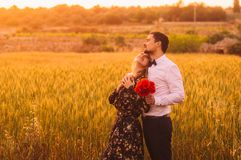 Man and woman with bouquet of poppies in wheat field on the dusk. Man and women with bouquet of poppies in wheat field on the dusk, Malta stock photos