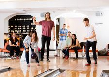 Man And Woman Bowling With Friends in Background Stock Image