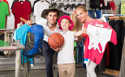 Man and woman with boy choosing all for hiking in sport shop Royalty Free Stock Photos