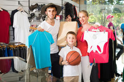 Man and woman with boy choosing all for hiking in sport shop Royalty Free Stock Images