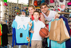 Man and woman with boy choosing t-shirts and other goods in spor Stock Photography