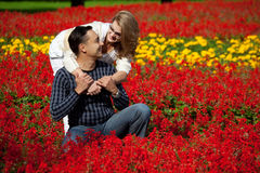 Man and woman in braces laughing in the flowers Royalty Free Stock Photography