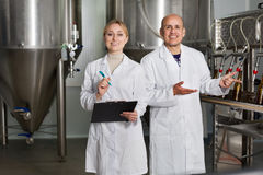 Man and woman among brewery equipment Royalty Free Stock Photos