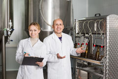 Man and woman among brewery equipment Stock Photos